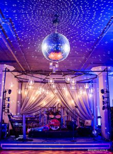 band set up on stage, mirror ball hanging from ceiling