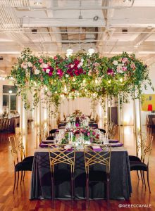 beautifully decorated reception table with flowers hanging above