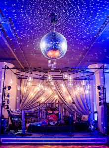 stage set up for band with mirror ball hanging from ceiling